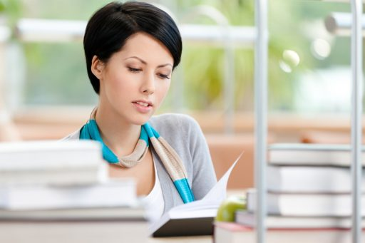 Young woman reads sitting at the desk
